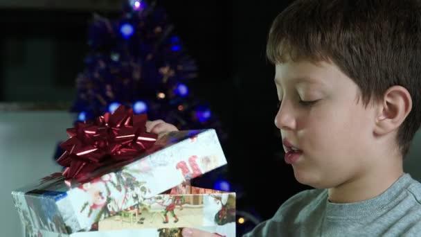 glückliches Kind öffnet ein Geschenk in der Weihnachtszeit