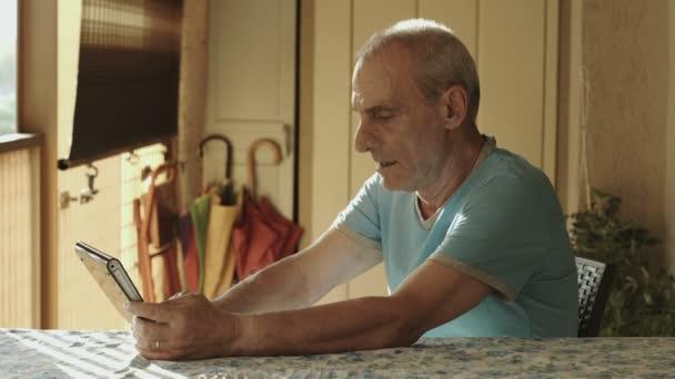 alter Mann nutzt Tablet-Computer zu Hause: Senioren, Technik, Internet