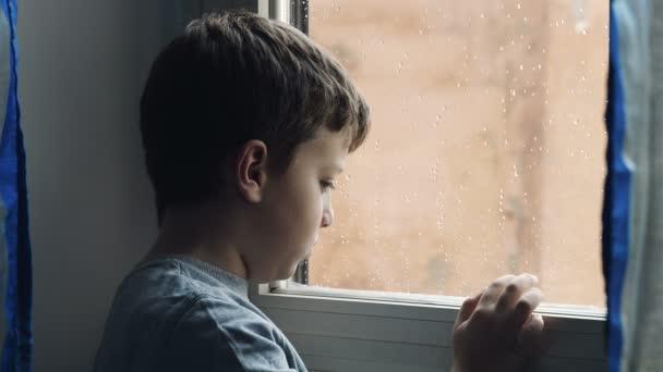 promyšlený a smutné dítě hraje s prstem na vlhké okno v deštivý den