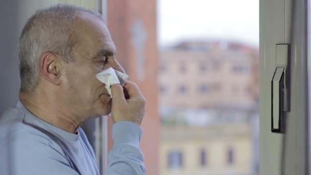 Starší muž s chladným vysmrkala se kapesník a kýchá