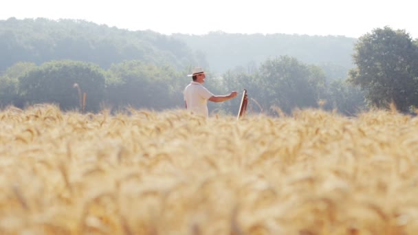 painter in the middle of a wheat field paints a beautiful landscape, easel