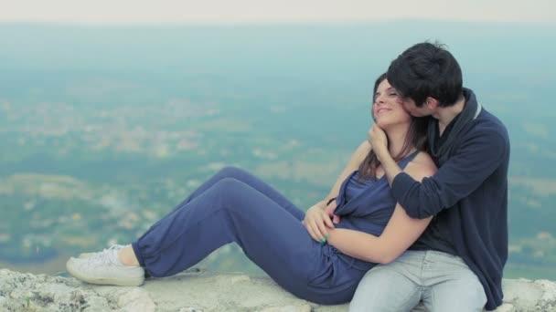 mladý muž objímá a líbá krásná mladá žena