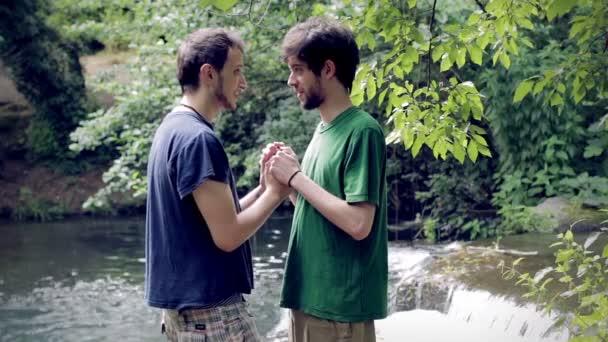 Láska. Polibek. Dva mladí gay muž s jezerem v pozadí