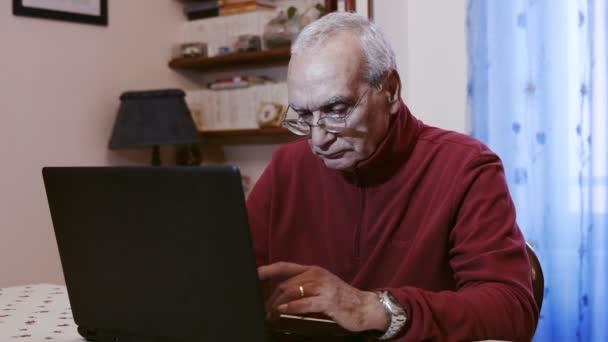 Alter Mann mit einem Persona-Laptop-Computer zu Hause