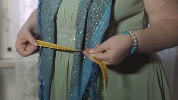 Tlustá žena držící měřicí páska