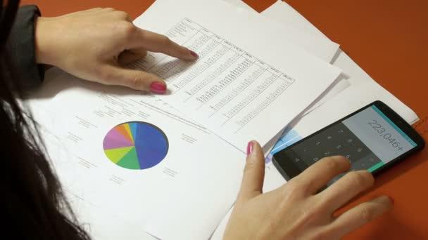 žena s kalkulačku a dokumenty