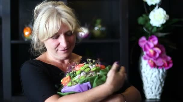 blonde woman of middle age in love hugging a bouquet of colorful flowers