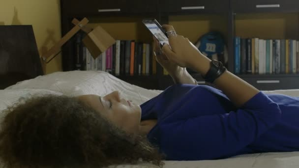 Young curly woman surfs the internet with your smartphone: Mobile phone, 4k
