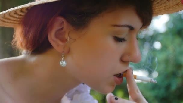 fiatal nő a dohányzás, a parkban