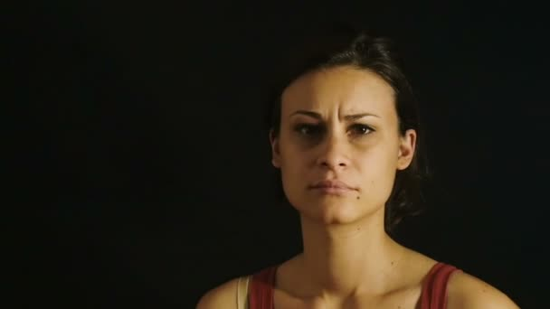 sad woman looking into the camera in the darkness: dark background