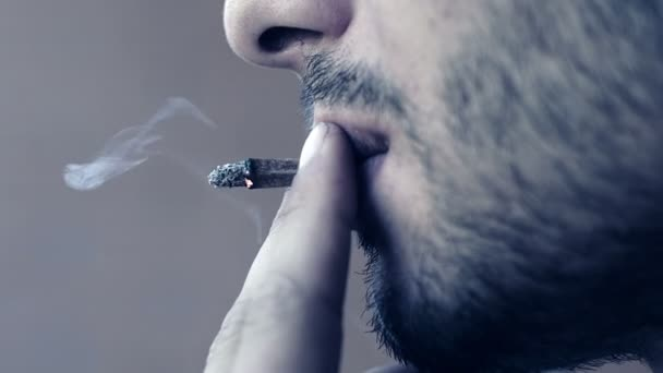 Side view of a casual fashion man smoking a marijuana joint