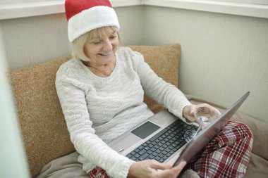 Safe online celebration. Senior woman holding a glass of wine and celebrating Christmas with her family virtually via internet and notebook at home. Video call. Distant holiday, indoor lifestyle
