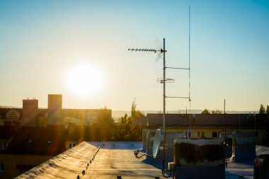 simple antenna mast with antennas and satellite dish to receive digital TV signals, DVB-T, DVB-T2, DVB-S, DVB-S2 and FM radio signals and delayed lightning rod. Warm lighting.