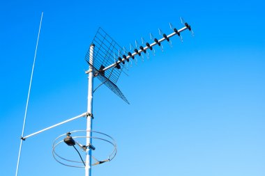 simple antenna mast with antennas to receive digital TV and radio signals, DVB-T, DVB-T2 and FM (horizontal polarization) including delayed lightning rod. The background is pure blue sky.