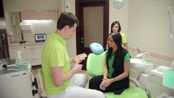 Zahnarzt zeigt Patientin Kiefergrundriss