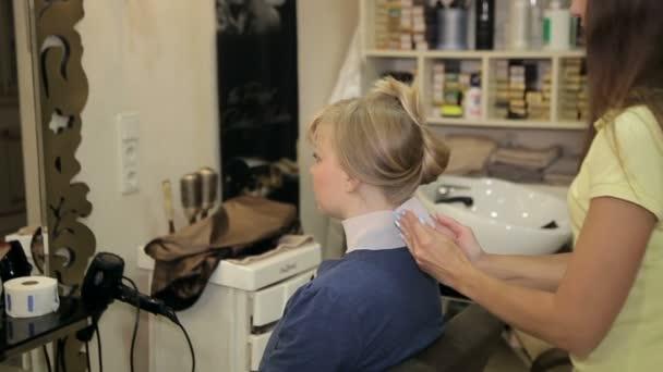 Barber připravuje klienta k účesu
