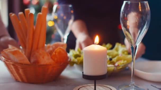 Slide shooting along festive table on which hands put dishes. Christmas family dinner, family puts food on table, camera movement along table