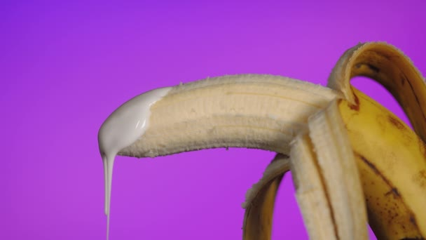 Concept of venereal diseases. Drops of yogurt dripping from end of banana on purple background. Veiled problems with male sexual organ