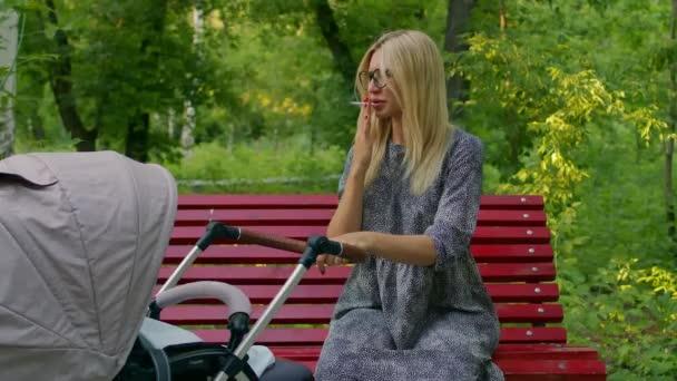 Mladá matka s kočárkem sedí na lavičce v parku a kouří. Dívka s brýlemi sedí na lavičce v parku, houpe kočárkem, kouří cigaretu a podezřívavě se dívá ze strany