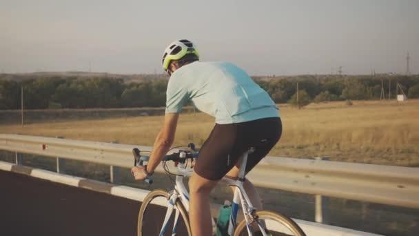 Cyklista muž na vysokorychlostním kole projíždí podél silnice na dálnici, na pozadí pole a města, pohled zezadu