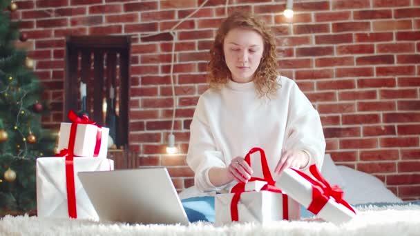 Mladá žena balí vánoční dárky v posteli. Příprava prázdninových boxů podle pokynů z internetu přes notebook. Kudrnaté vlasy žena váže luk na dárkové krabici při pohledu na ni
