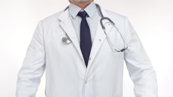 Doktor stojí ve studiu a zkříží ruce na prsou. Doktor uniforma s close-up stetoskop klade ruce v kříži.