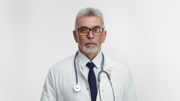 Studiový lékař v uniformě se stetoskopem a brýlemi se podívá do kamery a zkříží ruce na prsou. Dospělý lékař zkříží ruce se zkříženýma rukama.