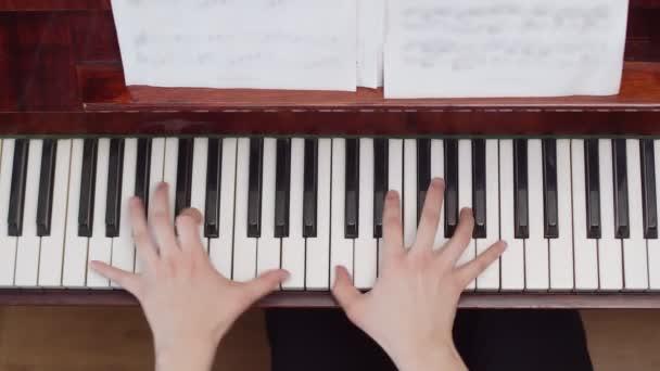 Musiker, der mit den Händen Klavier spielt, von oben gesehen. Künstler spielt Akkorde nach Noten auf Klaviertasten. Konzept Musikerziehung.