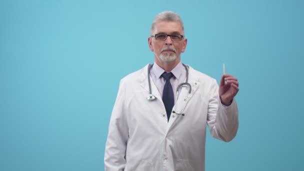 Az orvos egy cigarettát tart a kezében, és negatívan mozgatja az ujját, miközben a stúdió kék hátterét nézi. Fogalom a káros dohányzás és az egészséges életmód.