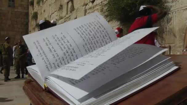 JERUSALEM, ISRAEL - MAY: Book of torah in Jerusalem. People walking by wailing wall in background