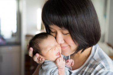 Asian mother holds her  newborn baby