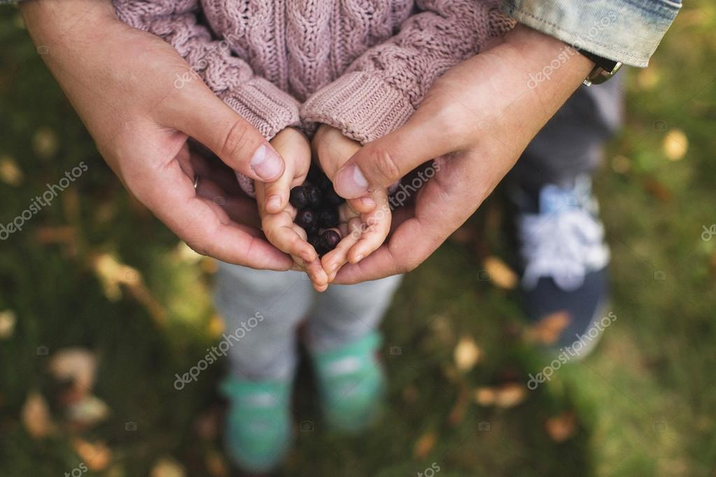 girl holding hands in berries