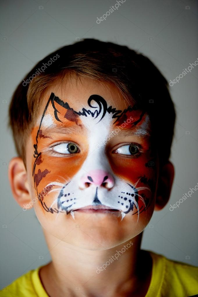 Years old boy with blue eyes face painting of a cat or tiger
