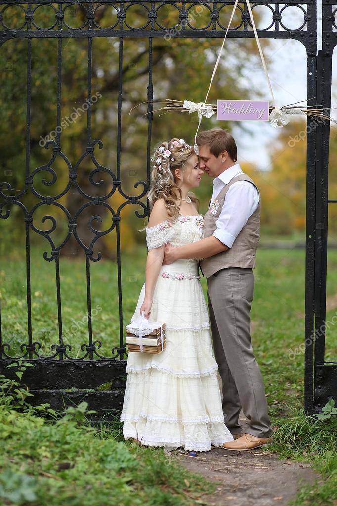 Retro style wedding couple hugging inside black iron gates