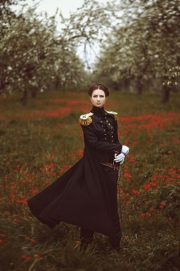 Magical pretty girl with sword stands in a field of flowers. The wind ruffles coat