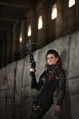 Raider girl in leather costume with a crossbow at post-apocalyptic world.