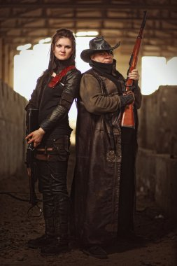 Man with rifle in a leather garment and woman in raider costume with crossbow inside a concrete shelter.