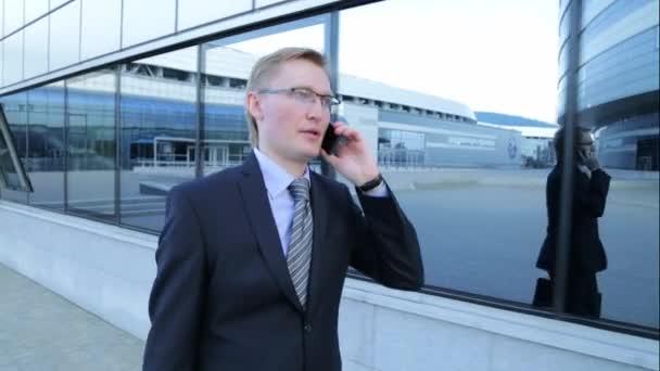 Junger Geschäftsmann ist Fuß und telefonieren (Steadicam Schuss)
