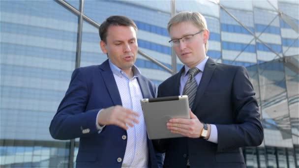 Zwei Geschäftsleute, die mit digitalen tablet-Computer Touchscreen, über die Arbeit reden
