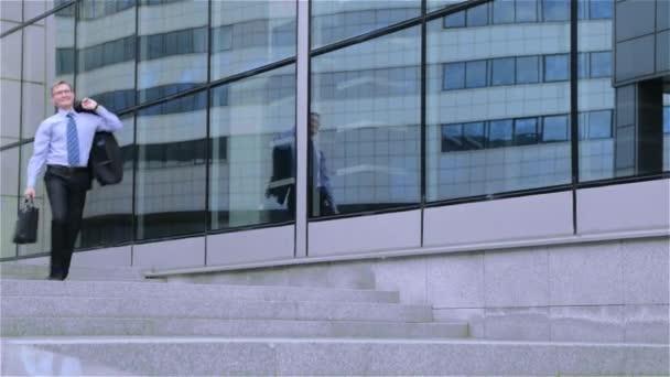 Glücklicher junge Geschäftsmann geht die Treppe in der Nähe von modernen Bürozentrum