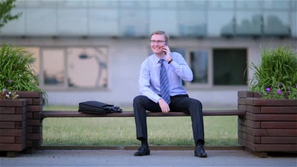 Glückliche junge Geschäftsmann am Telefon sitzen auf einer Bank in der Straße