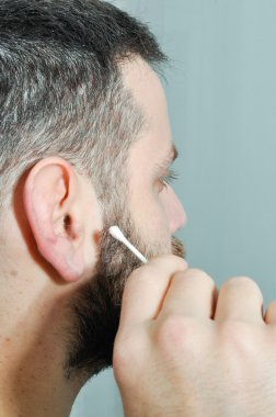 Man with the ear dirty. Young man cleaning his ear. Adult taking care of his body. Man with cotton buds.