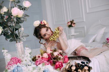Beautiful young sexy woman sitting on white bed and eating grapes, wearing white lace dress, room decorated with flowers. Perfect makeup. Beauty fashion. Eyelashes. Studio retouched shot.