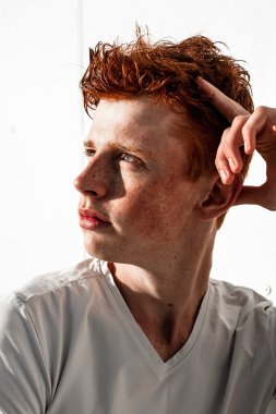 Portrait of attractive stylish young guy model with red hair and freckles standing near white wall , wearing white t-shirt. Fashionable outdoor shot.