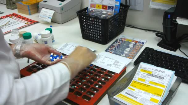 WYONG, AUSTRALIA - DEC 16 2012: a pharmacist packs a blister pack with pills