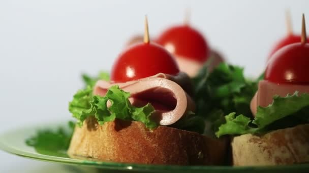 4 malé chutné sendviče s klobásou a zelení na bílém pozadí