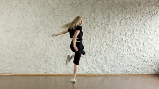 Young attractive girl dancing in the style of house in the dance hall