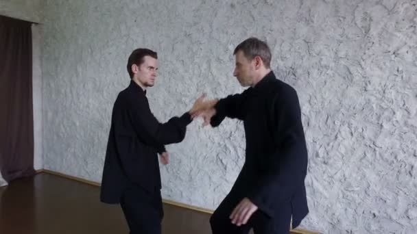 Training in the hall. Two men practicing the elements of tai chi. 4K