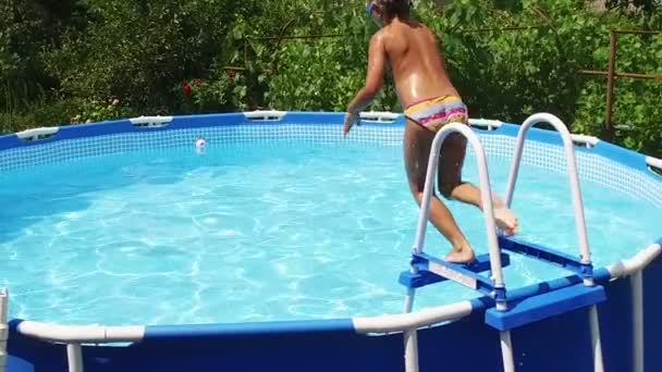 Swimming pool. Little girl jumping into the water in the pool. Slow motion. HD