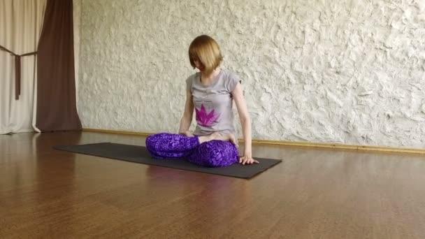 A fiatal szőke lány jóga a közös helyiségekben. A testtartás, a lotus. 4k